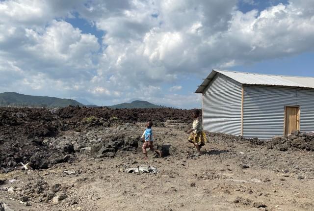 Des enfants de la ville viennent constater les dégâts près de la coulée de la lave séchée
